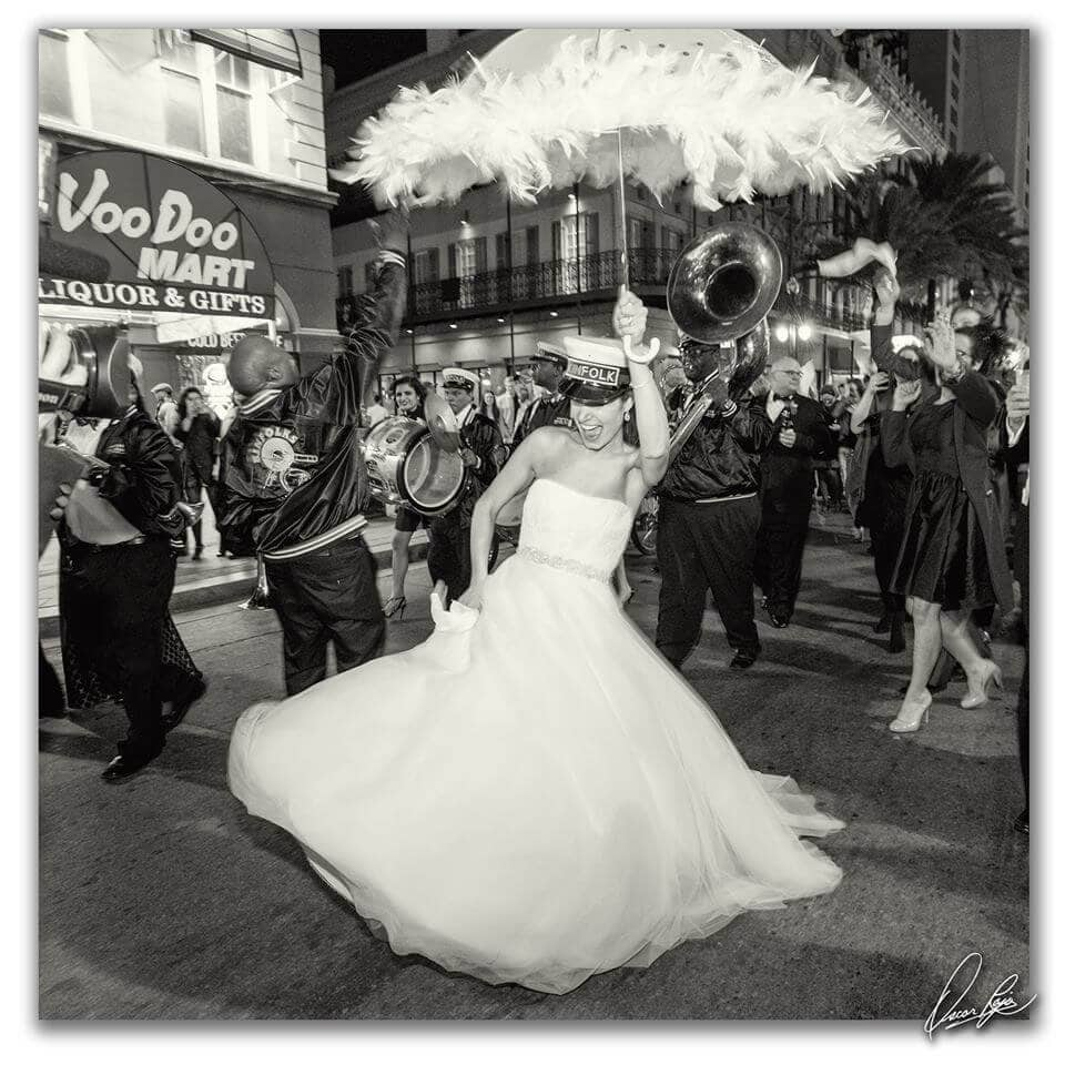 Bride in New Orleans parade with a feathery umbrella